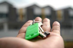 Mão aberta, com molho de chaves em um chaveiro verde, a frente imagem de casas ofuscadas